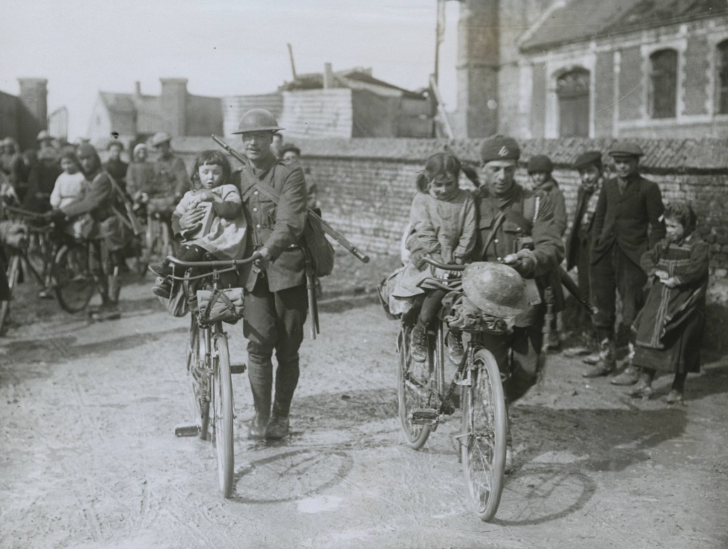 Official_Photographs_taken_on_the_British_Western_Front_in_France__Scene_in_a_newlycaptured_village__Children_soon_make_friends_with_Tommy